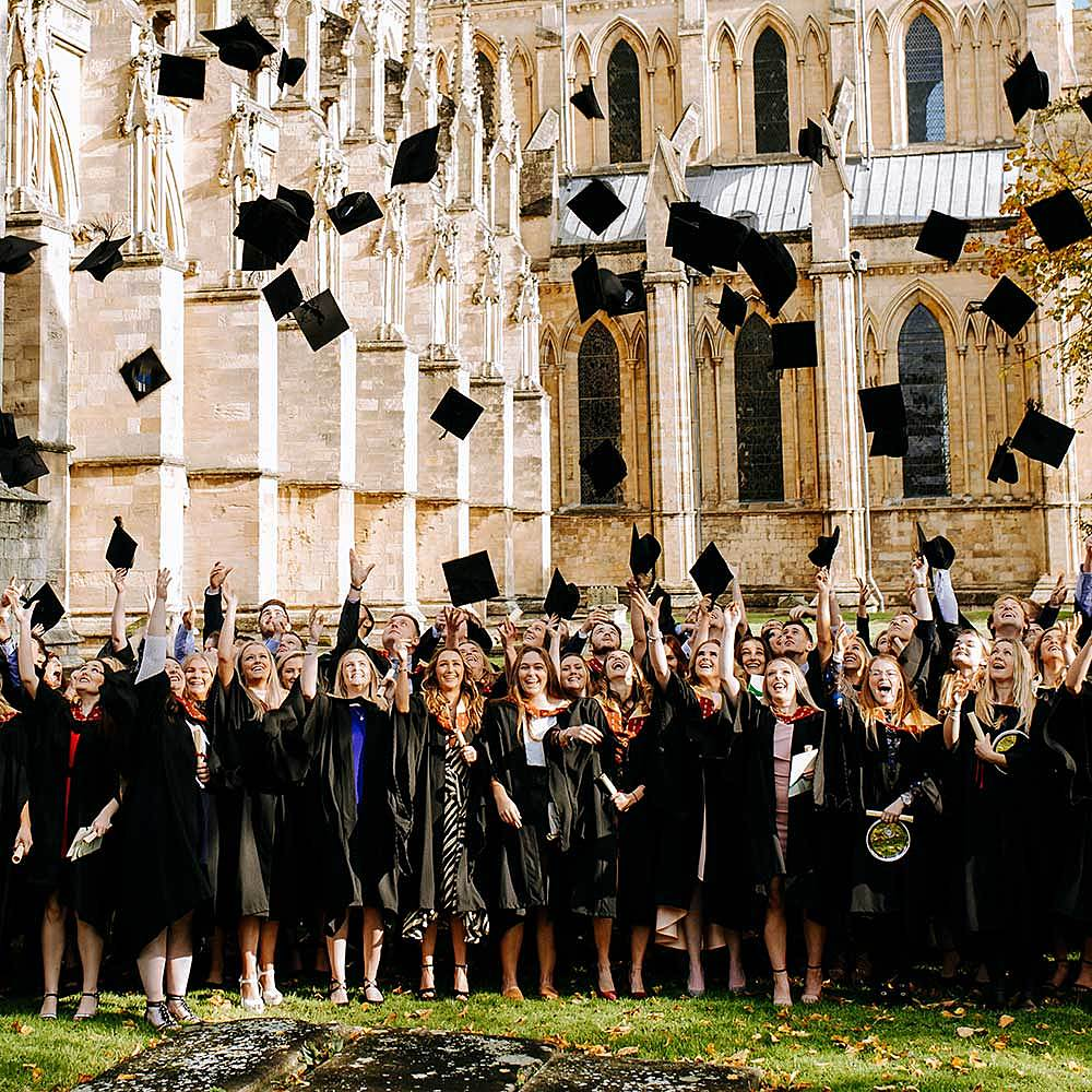 Degree students throwing caps outside Beverley Minster at Riseholme College graduation