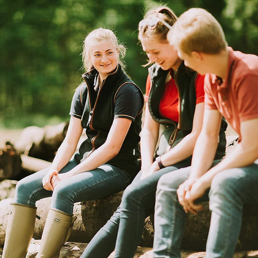 Agriculture students laughing sat on log in woodland at Riseholme College