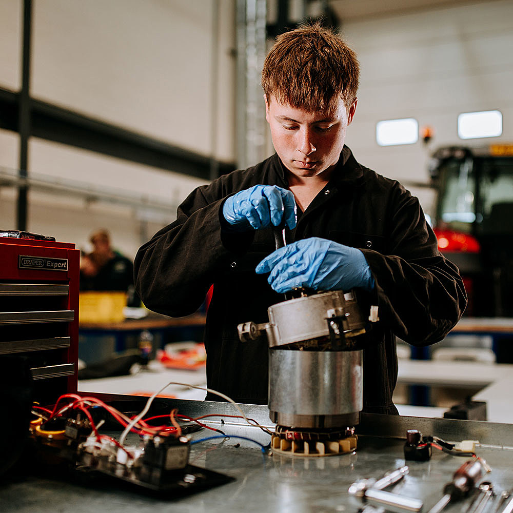 Engineering student/apprentice working on mechanical parts in workshop at Riseholme College