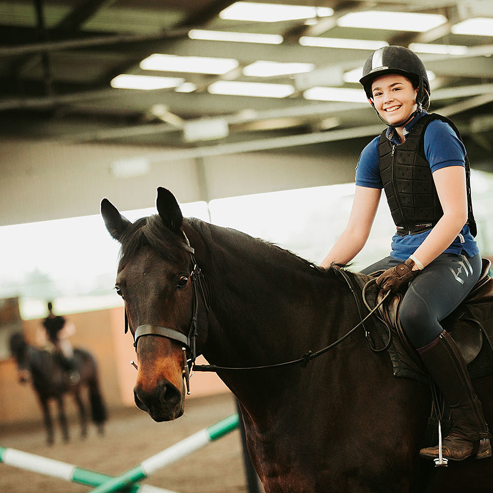 Equine student riding a horse in an indoor arena at Riseholme College's Equine Centre